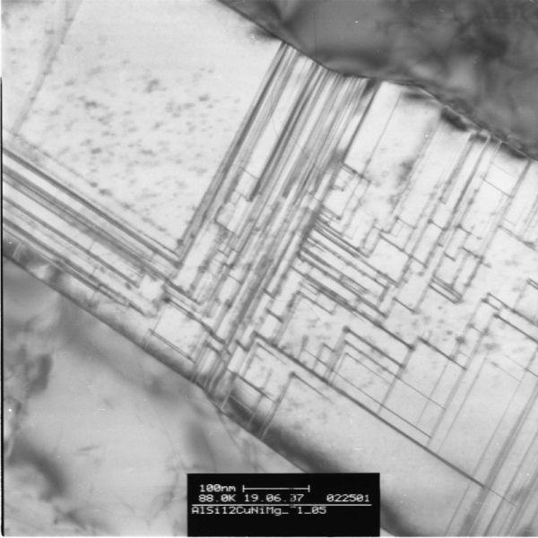 Bild 4: TEM-Bild, Hellfeld: Legierung Al Si12CuNiMg, Zustand T1 (aus der Gießhitze abgeschreckt und vollständig kaltausgelagert): Die feinen Linien charakterisieren Kohärenzspannungsfelder, die aufgrund der Gitterverzerrung in Umgebung der Ausscheidungen entstehen.