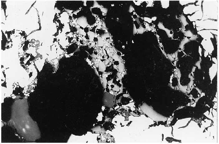 Fig. 2:  Micrograph through the zone shown in Fig. 1. Slag-like inclusions are clearly visible, magnification 100:1