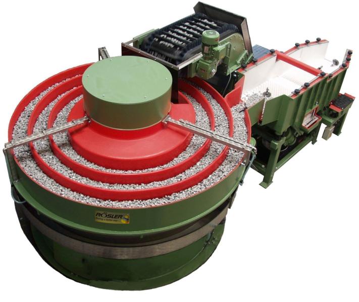 """Bild 3: Rundvibrator """"rotomatic"""", diese neue Maschinenreihe reduziert die Bearbeitungszeiten fast um die Hälfte gegenüber herkömmlicher Rundvibratorentechnik. Sie sind meist als vollverkettete Durchlaufanlagenlösung aber auch als Einzelanlage im Einsatz. Arbeitsbehälternutzlängen von 15 bis 27 m gewährleisten einen besonders hohen Werkstückdurchsatz.(Rösler Oberflächentechnik GmbH, Untermerzbach)"""