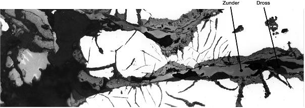 Bild 2: Detailaufnahme aus Bild 1, die Drossfehler sind innerlich stark verzundert. In Bereichen, in denen die Fehler noch geschlossen sind, findet man in der Zunderschicht Schlackenhäute (Dross) eingelagert, Vergrößerung 300:1