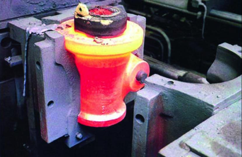 Bild 1: Zweiteilige Kokille im aufgefahrenen Zustand mit rot glühendem, aber bereits gestaltfestem Gussteil (Quelle: Rexroth Guss, Lohr),